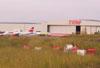 Pátio e hangar de manutenção da TAM. (Veja um Airbus 320 sendo empurrado pelo pushback e um Fokker 100 estacionado.)