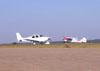 Cirrus SR-22 correndo para decolar e um Cessna 170-B, PT-APY, na taxiway.