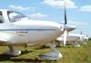 Aeronaves Cirrus estacionadas na grama ao lado do pátio da aviação geral.