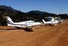 Piper/Neiva EMB-711ST Corisco II Turbo, PT-RHG, e outros aviões estacionados ao lado da pista. Foto: Wesley Minuano.