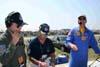 A partir da esquerda, o Capitão Aviador Afonso Henrique, um dos pilotos do Tucano número 4, se prepara para fazer a locução durante a apresentação da Esquadrilha da Fumaça, enquanto um técnico faz a instalação de equipamentos e Rob Reider, locutor oficial do evento entretém o público do Dayton Air Show, em Dayton, Ohio, Estados Unidos. (29/07/2007) Foto: Suboficial Waldemar Prieto Júnior, fotógrafo do Esquadrão de Demonstração Aérea.