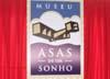Painel com o logotipo do museu, estendido no palco.