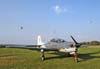 Embraer T-27 Tucano, FAB 1355, estacionado enquanto dois Tucanos da Esquadrilha da Fumaça se separam no céu de Piracicaba. (02/09/2007) Foto: GAFAB (02/09/2007)