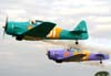 Decolagem dos aviões da Esquadrilha Oi. A partir da direita, o North American T-6D, PT-LDQ, aeronave número 2 (roxo), pilotado pelo Laert Gouvêa, e o North American T-6D, PT-KRC (verde), aeronave número 1, pilotada pelo Comandante Carlos Edo. Foto: Bruno Schmidt.