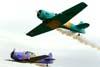 Pill-off dos aviões da Esquadrilha Oi. A partir da esquerda, o North American T-6D, PT-LDQ, aeronave número 2 (roxo), pilotado pelo Laert Gouvêa, e o North American T-6D, PT-KRC (verde), aeronave número 1, pilotada pelo Comandante Carlos Edo. Foto: Bruno Schmidt.