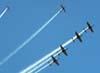 Embraer T-27 Tucanos, da Esquadrilha da Fumaça, se dispersando da formatura Cobrinha-show realizando um Immelmann, fazendo um leque de fumaça no céu, posicionando os aviões para a passagem individual de despedida.