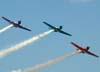 Os aviões da Esquadrilha Oi voando em formação. À partir da esquerda, o North American T-6D, PT-LDQ, aeronave número 2 (roxo), pilotada pelo Leandro, o North American T-6D, PT-KRC (verde), aeronave número 1, pelotada pelo Comandante Carlos Edo, e o North American T-6D, PT-LDO, aeronave número 3, pilotada pelo Hernani.