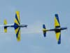 """Os Embraer T-27 Tucano número 5, comandado pelo Tenente Aviador Márcio, e número 6, pilotado pelo Capitão Aviador Caldas, da Esquadrilha da Fumaça, realizando a """"Panqueca""""."""