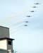"""Os Embraer T-27 Tucano 1, comandado pelo Major Aviador Davi, 2, pilotado pelo Tenente Aviador Anderson Amaro, 3, pilotado pelo Tenente Aviador Baldin, 4, comandado pelo Tenente Aviador Felzcky, 5, pilotado pelo Tenente Aviador Márcio, e 6, comandado pelo Capitão Aviador Caldas, da Esquadrilha da Fumaça, voando na formatura """"Cobrinha Show"""" antes da separação individual das aeronaves. Note nesta foto a presença de um edifício, aliás, havia vários edifícios próximos a área de exibição."""